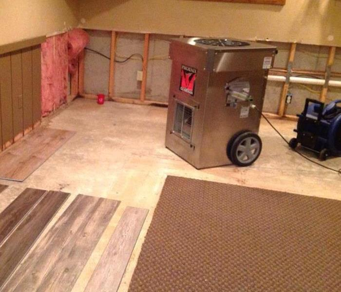 A large air dryer sits in the middle of a basement floor that has had portions of carpeting removed.