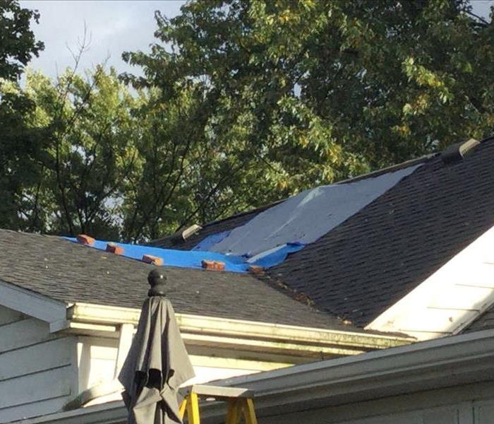 A blue tarp covers a portion of the roof of a residential home.