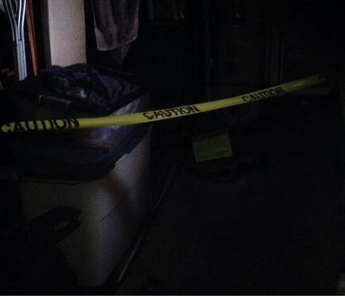 A soot covered room lined with caution tape